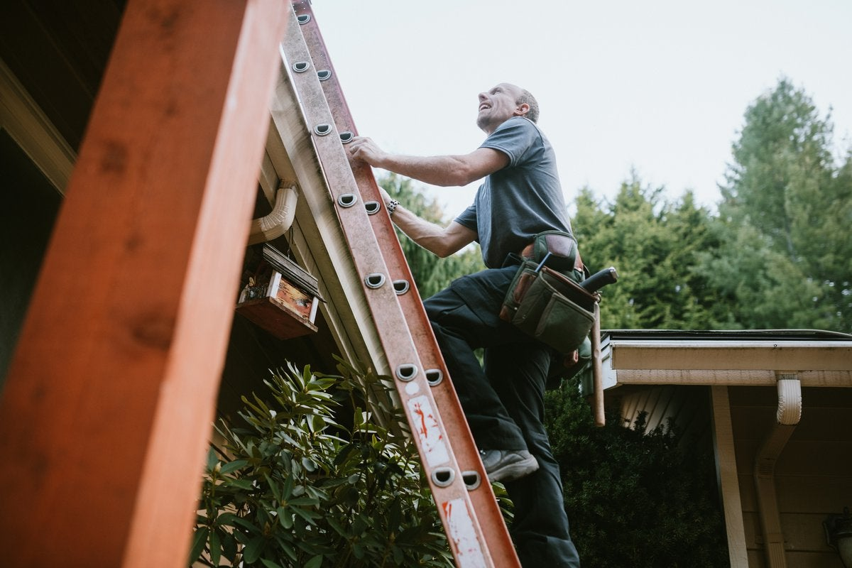 Man with tool belt climbing ladder to roof.