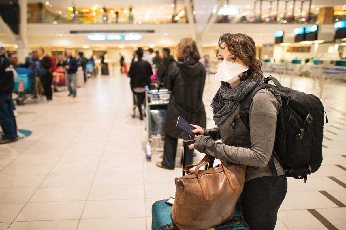 Masked woman with luggage waiting in a busy airport.