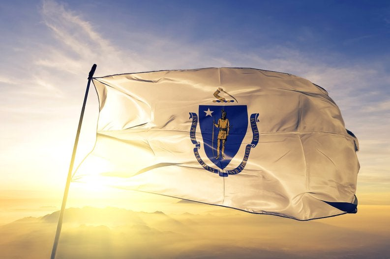 The Massachusetts state flag flying in front of a sunny sky.