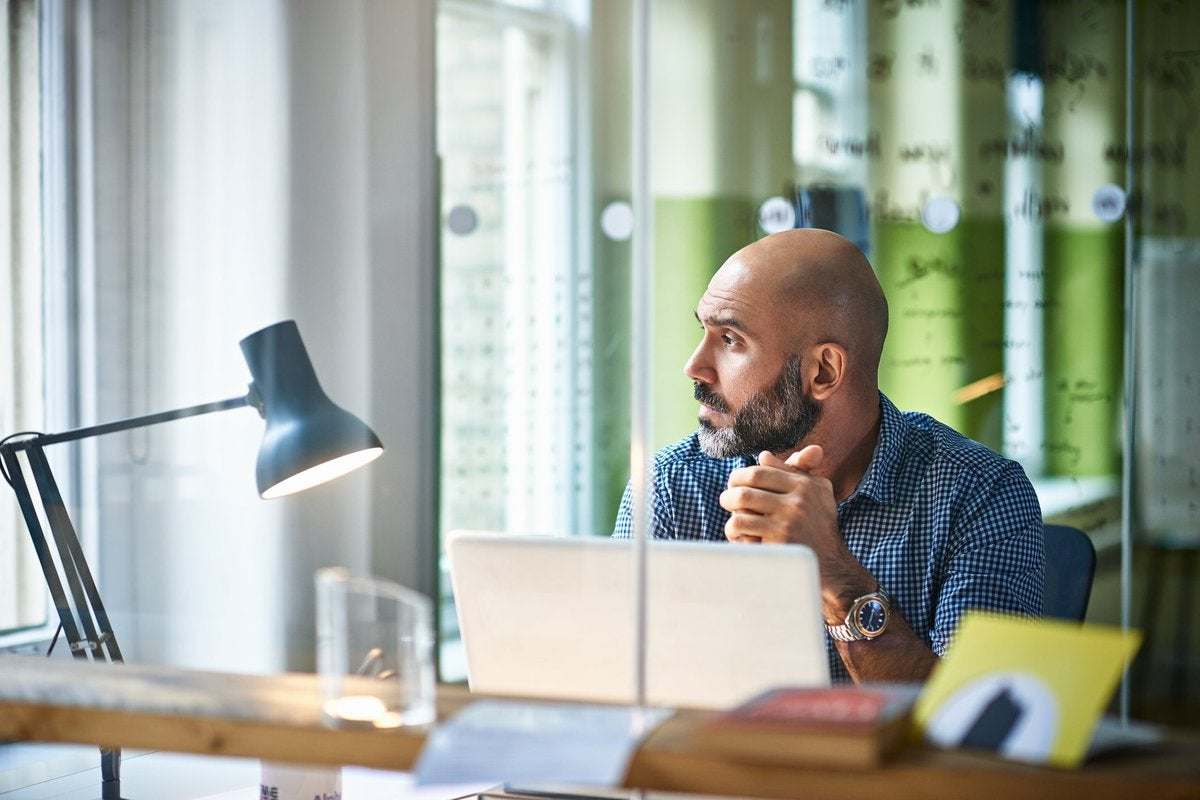 Mature man at desk looking off in thought.