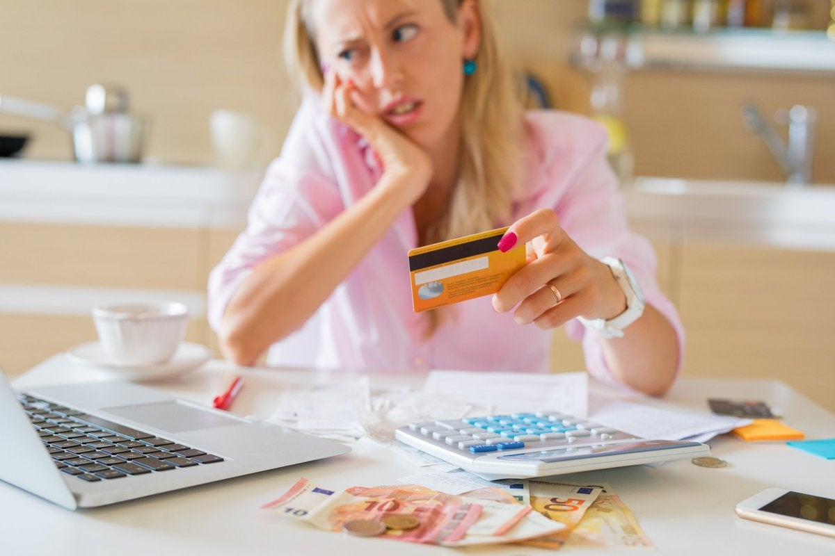 Woman looking at laptop in dismay as she holds a credit card in her hand.