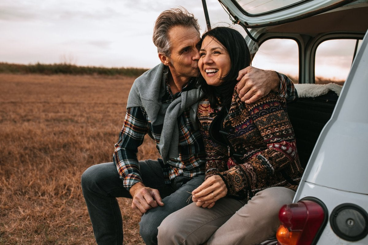 A middle-aged couple sitting in the open trunk of their car in a field with their arms around each other.