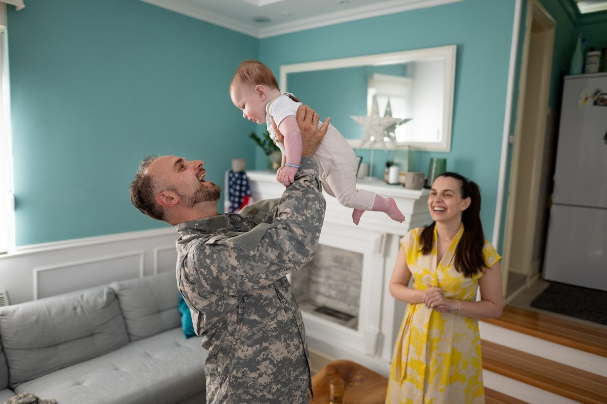 Military family enjoying time together inside home with toddler.