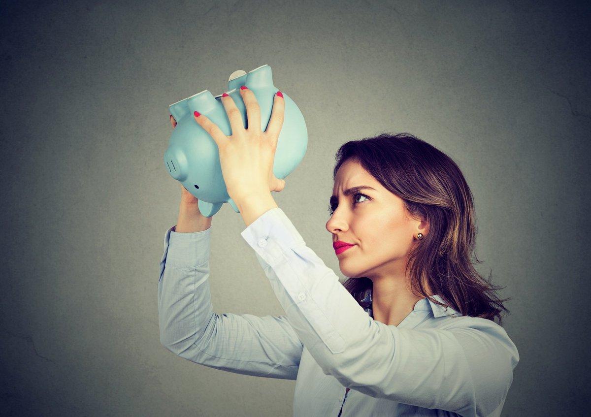 woman holding empty piggy bank upside down