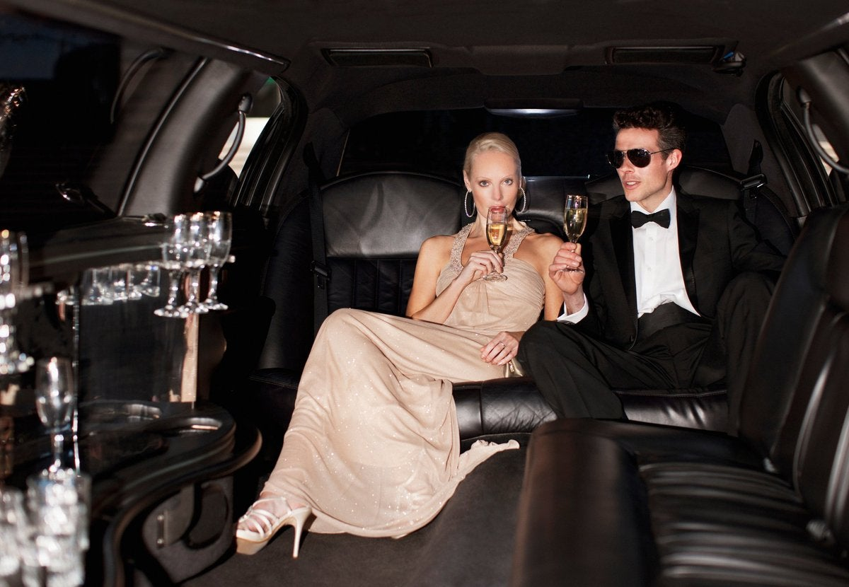 Two young millionaires in a limo drinking champagne