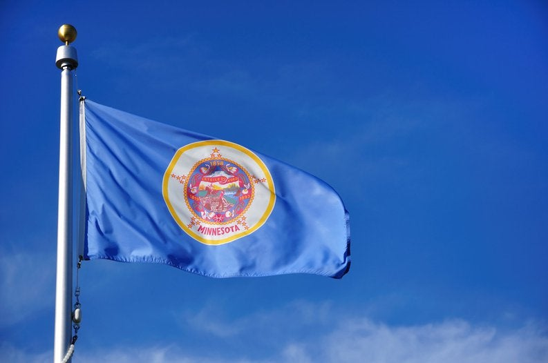 The Minnesota state flag waving in front of a blue sky.