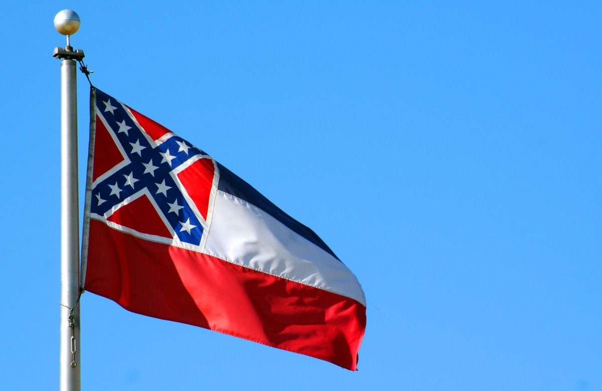 The Mississippi state flag flying in front of a blue sky.