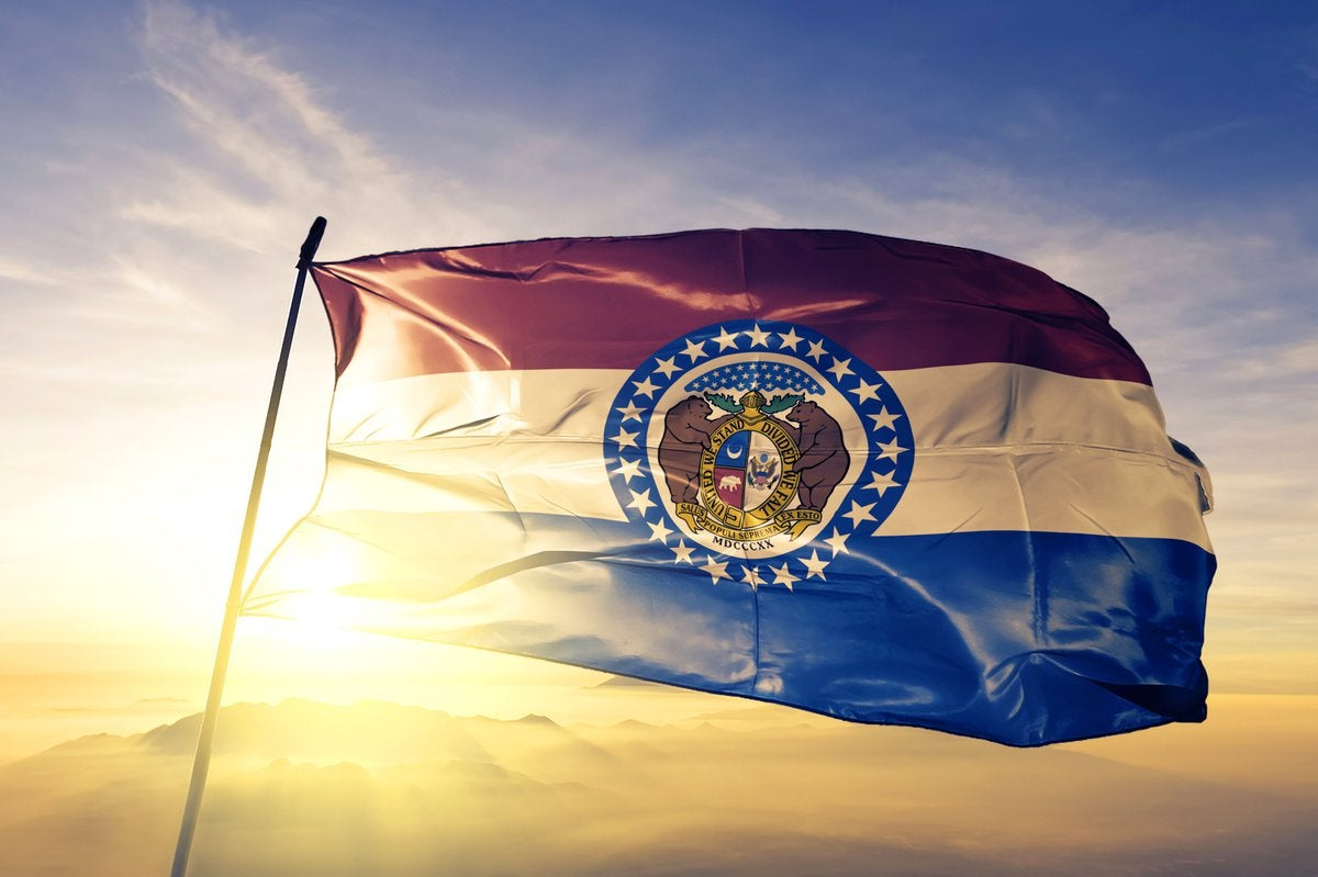 The Missouri state flag in front of a sunny sky.