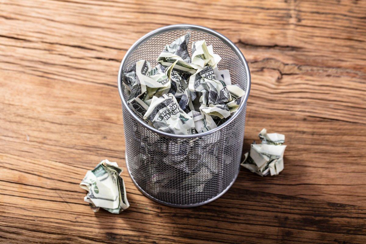 Crumpled dollar bills in a trash can.