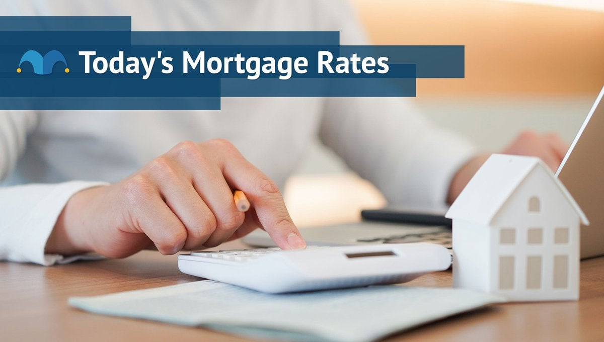 Hand typing on a calculator next to small model home with Today's Mortgage Rates graphic.