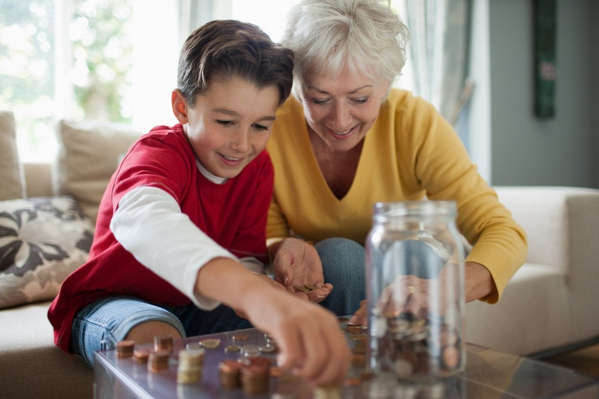 Grandmother teaching boy how to save coins in a jar.