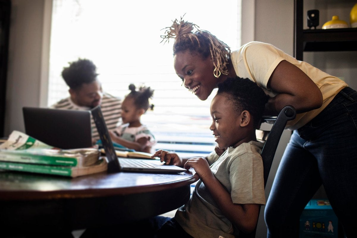 Mother helping young child with e-learning on laptop.