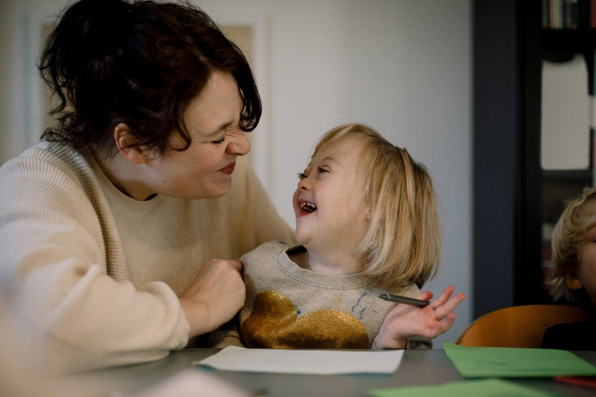 Mother making facial expressions while playing with disabled daughter at dining table.