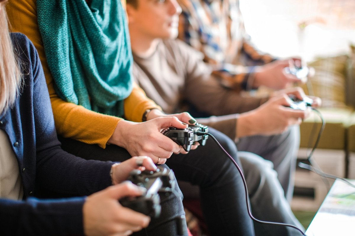 Multiple people sitting on a couch holding gaming controllers.
