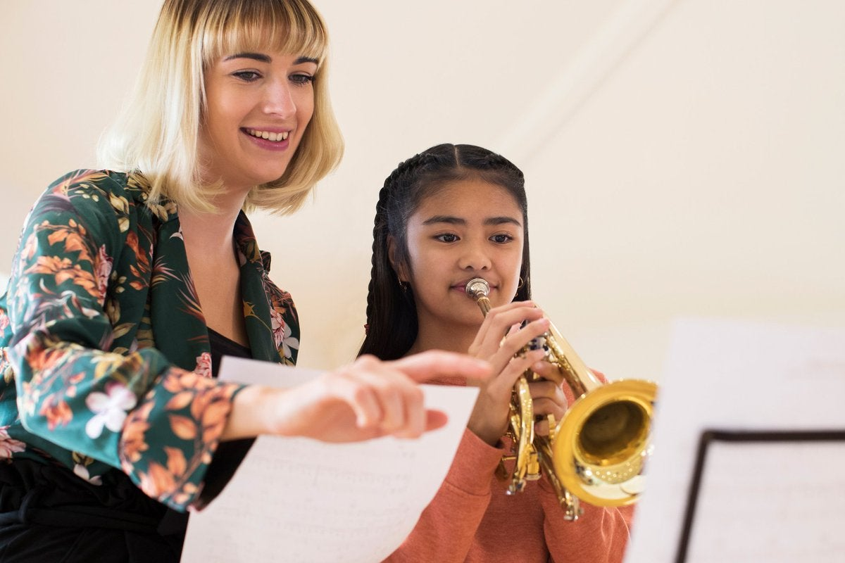 A smiling female teacher instructing a young girl playing a trumpet.