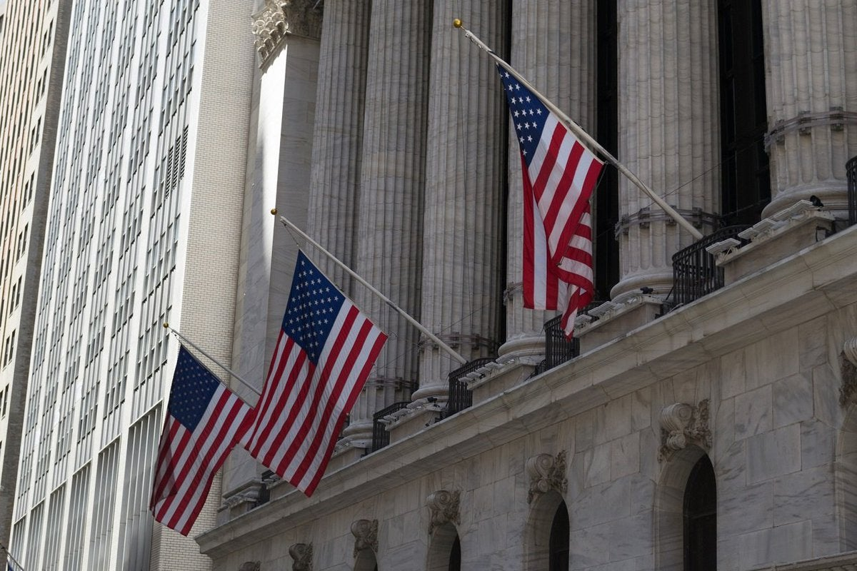 Three American flags hanging from building with concrete pillars.