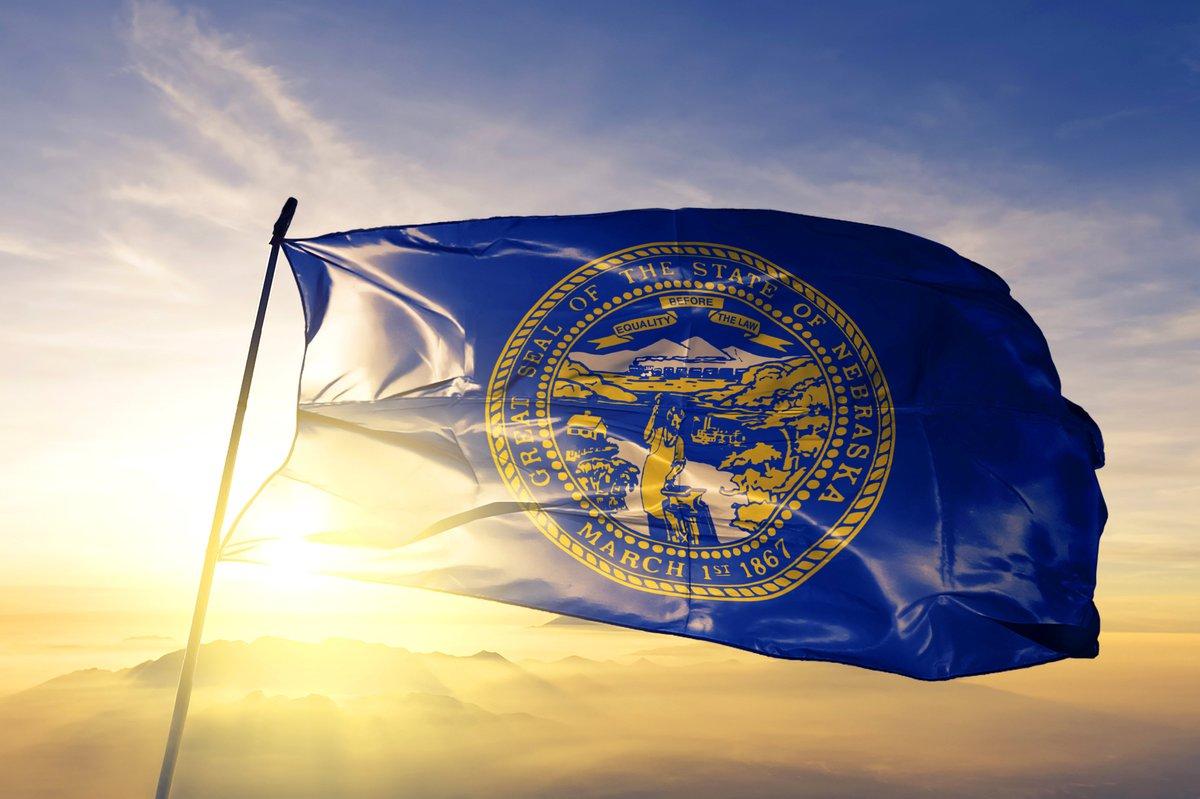 The Nebraska state flag flying in front of a sunny sky.