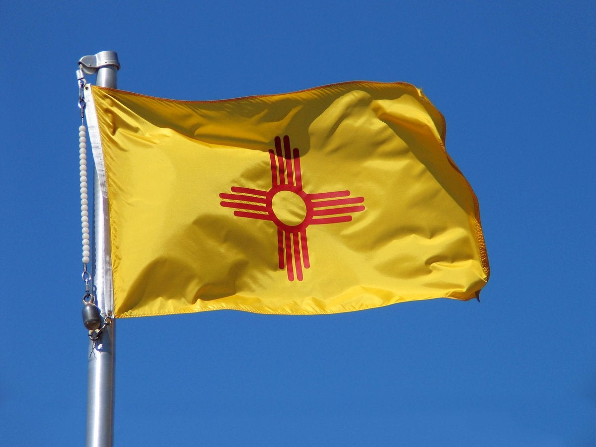 The New Mexico state flag in front of a blue sky.