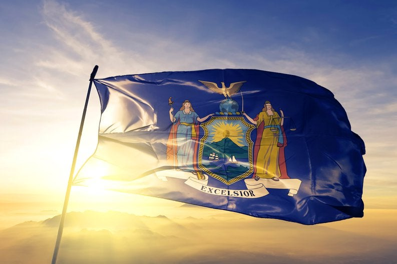 The New York state flag flying in front of a bright sun.