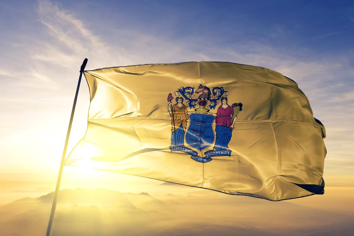 The New jersey state flag flying in front of a sunny sky.