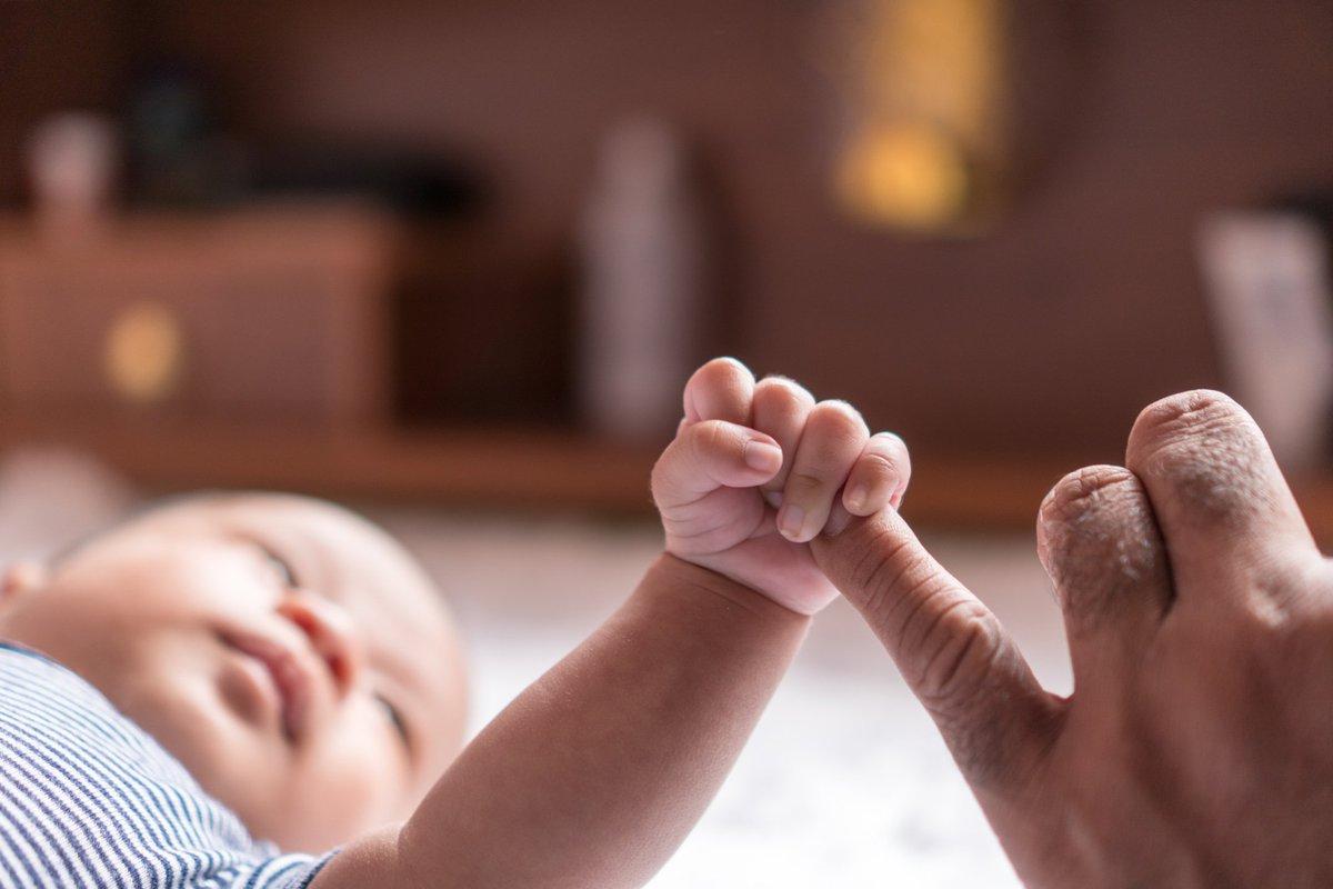 Newborn baby gripping parent's pinky finger.