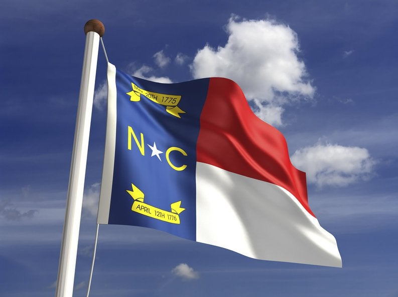 The North Carolina state flag in front of a blue sky with white clouds.