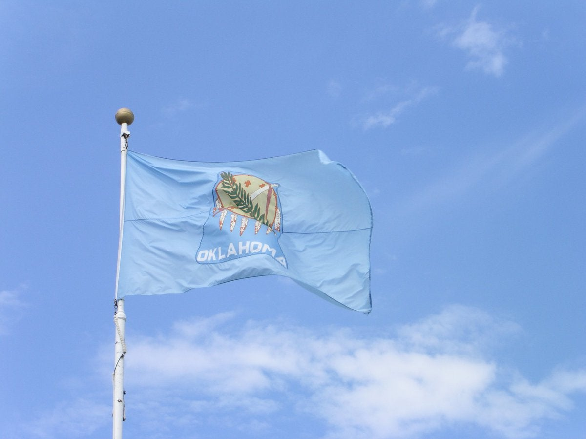 The Oklahoma state flag in front of a blue sky and white clouds.