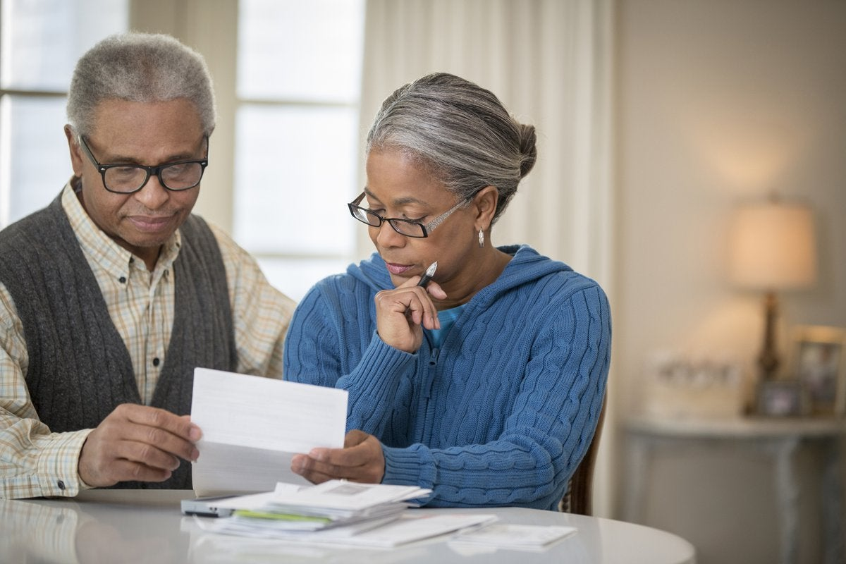 An older couple sit at a table and go over their finances.