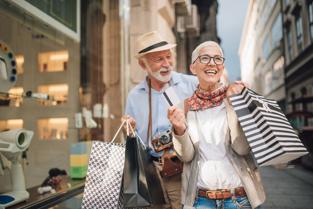 An older couple, out on a credit card spending spree, are shown walking down a street, holding shopping bags and smiling.