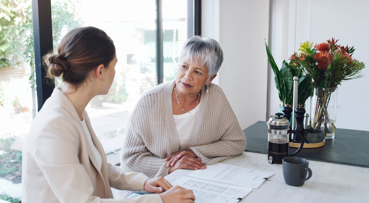 An older woman has a conversation over paperwork with a young professional.