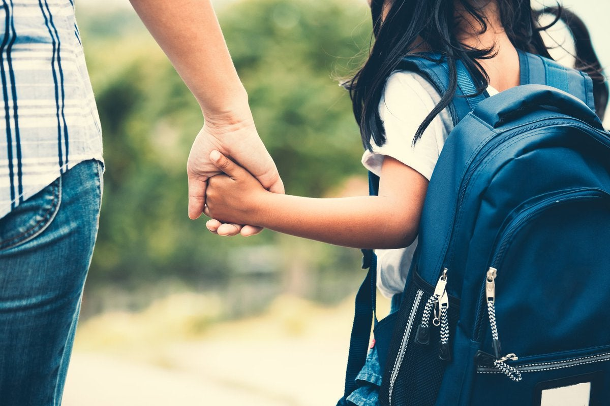 A parent holding hands with their young child wearing a backpack.
