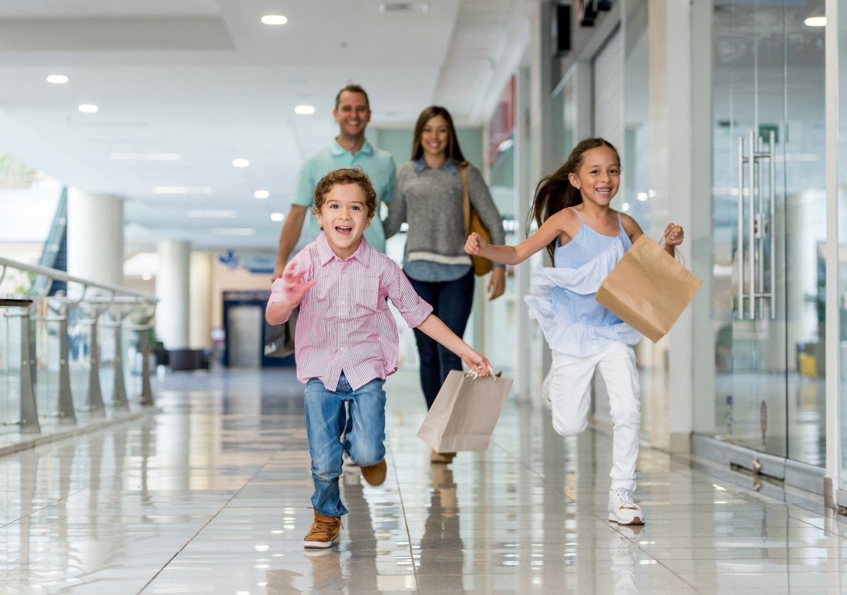 Parents and kids at shopping mall with shopping bags.