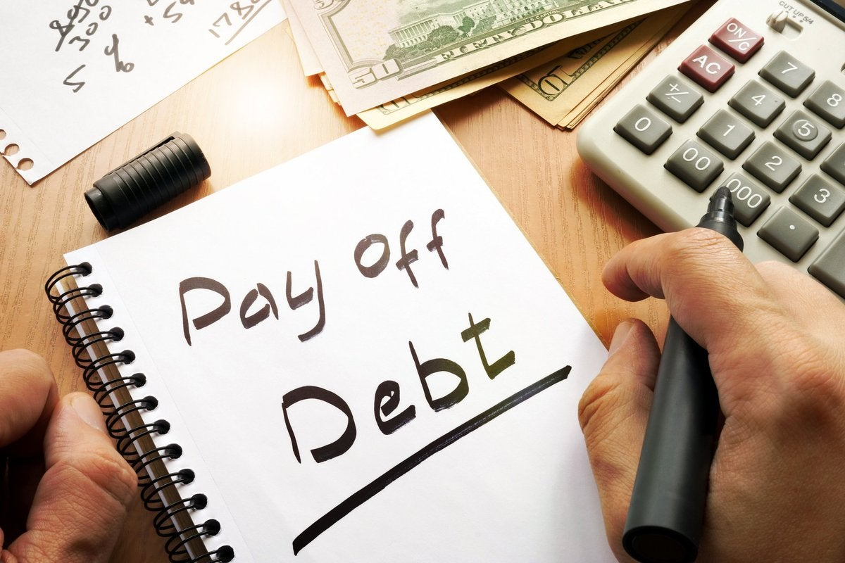 "A notepad with ""Pay off debt"" written in black marker."
