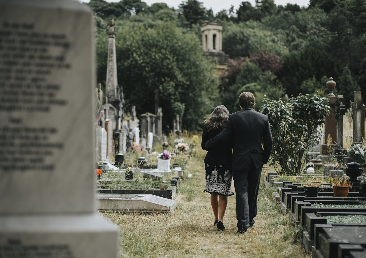 A man and woman attending a funeral.
