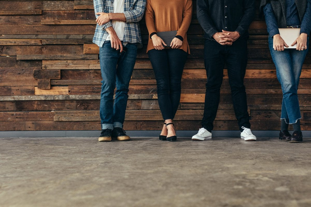 Four people standing against a rustic wood wall.