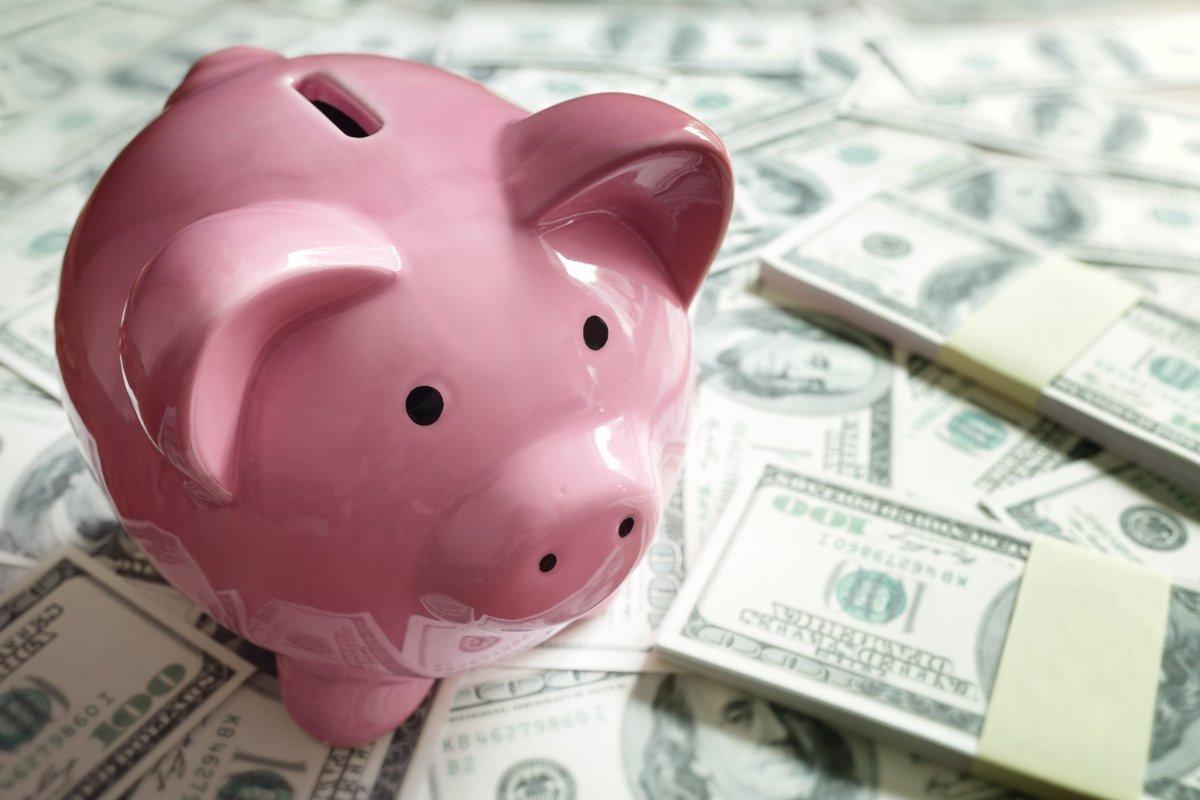 Pink piggy bank on top of piles of hundred dollar bills.