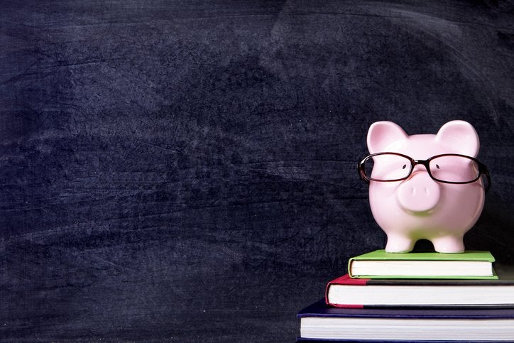 Piggy bank wearing glasses sitting on stack of books in front of classroom chalkboard.