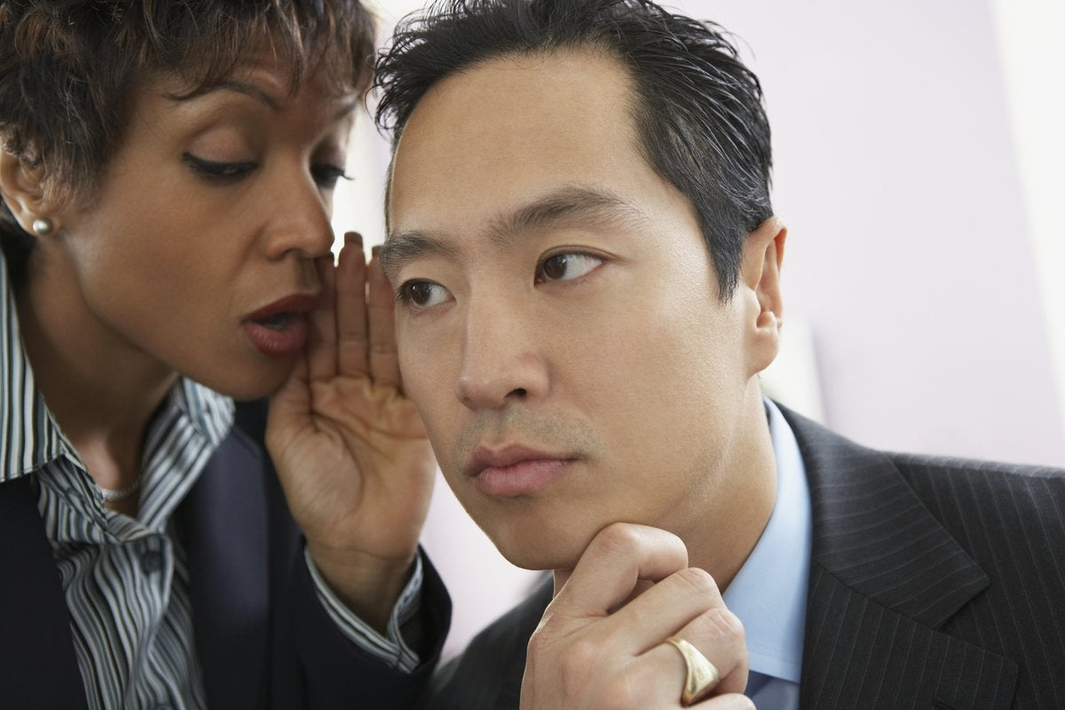 Professionally dressed woman whispering in the ear of professionally dressed man.
