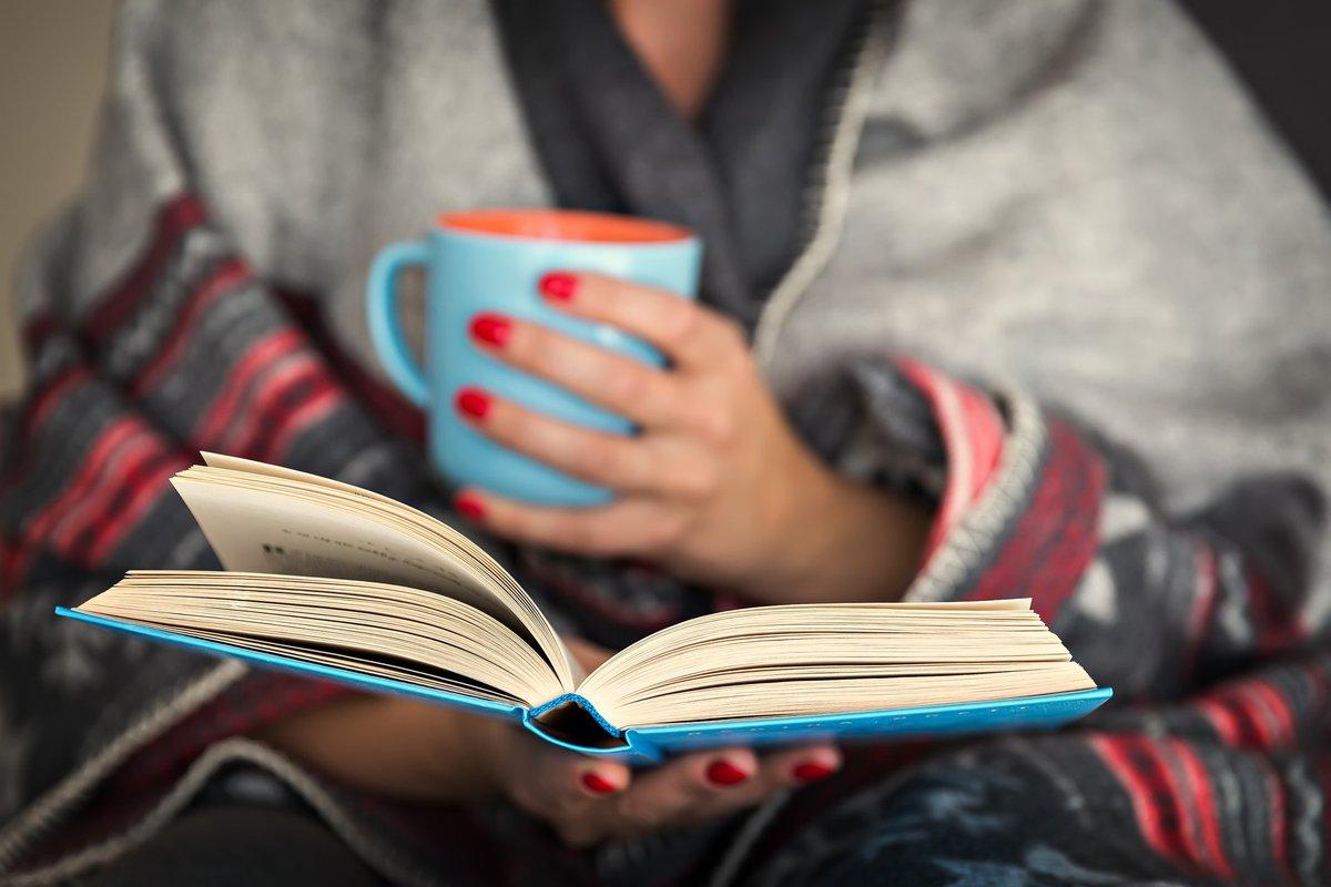Woman holding a mug, reading a book
