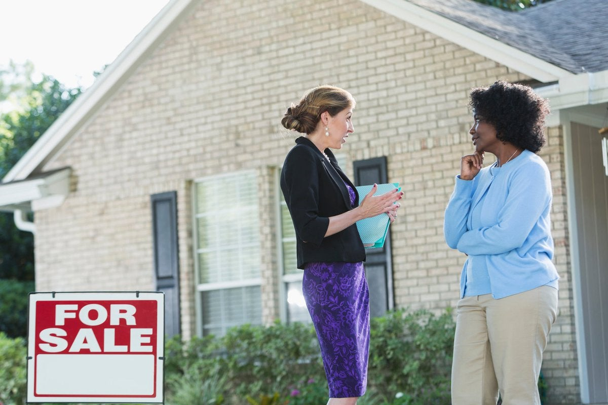 A real estate agent talks with a potential homebuyer outside of a home.