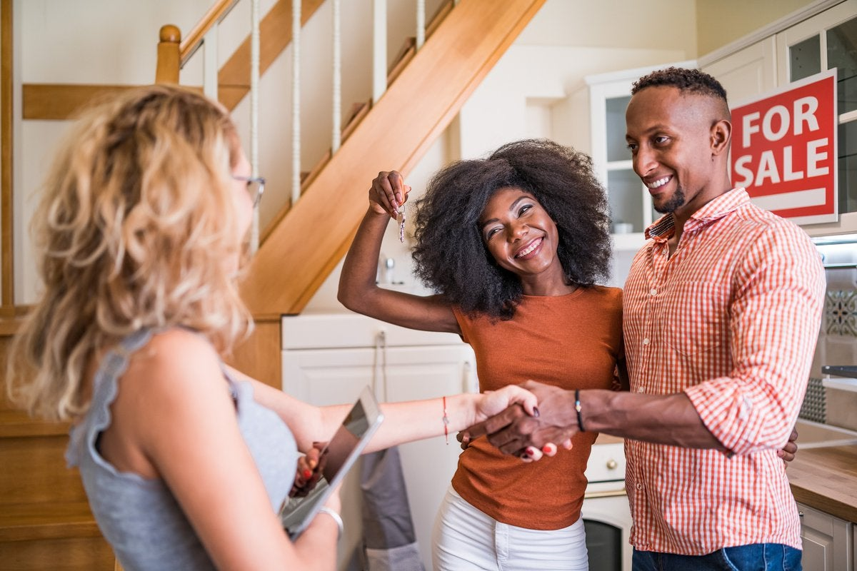 Real estate agent congratulating a new owner for buying new house