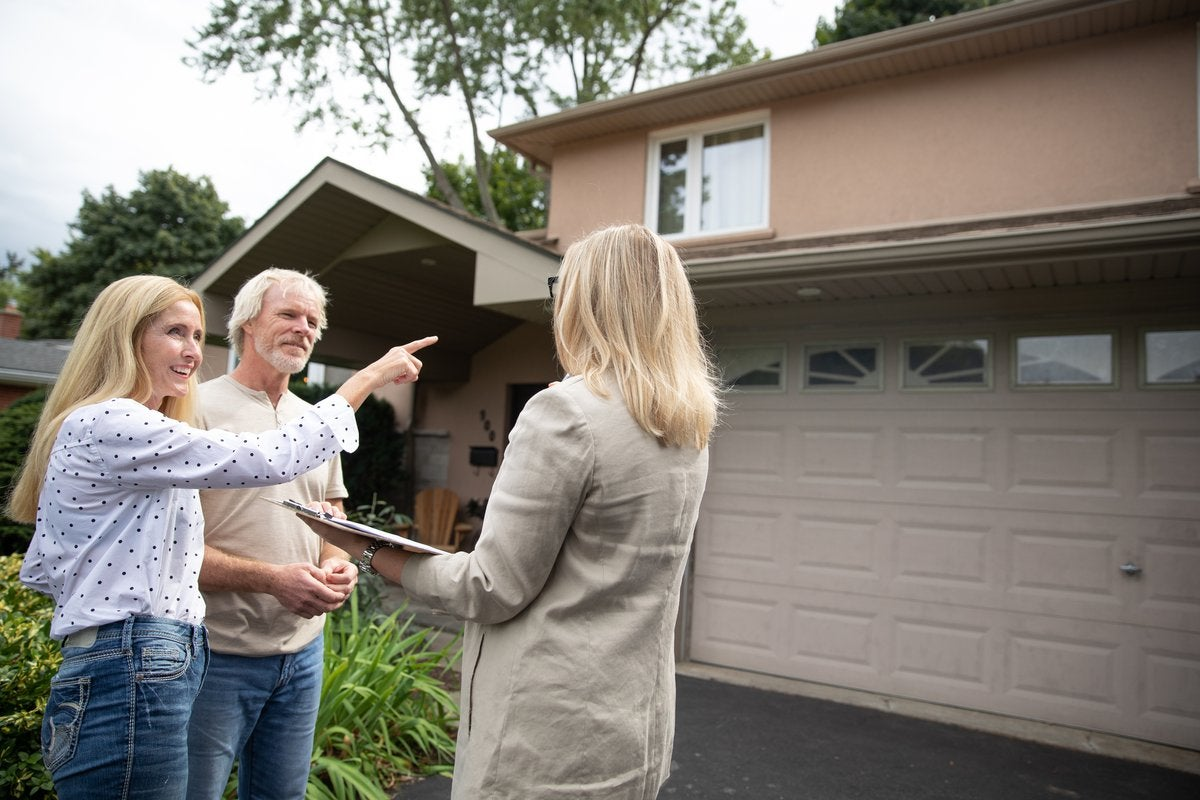 Real estate agent shows mature couple a property.