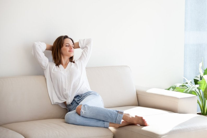 A relaxed woman stretching her arms above her head while sitting on her couch in a sunny apartment.