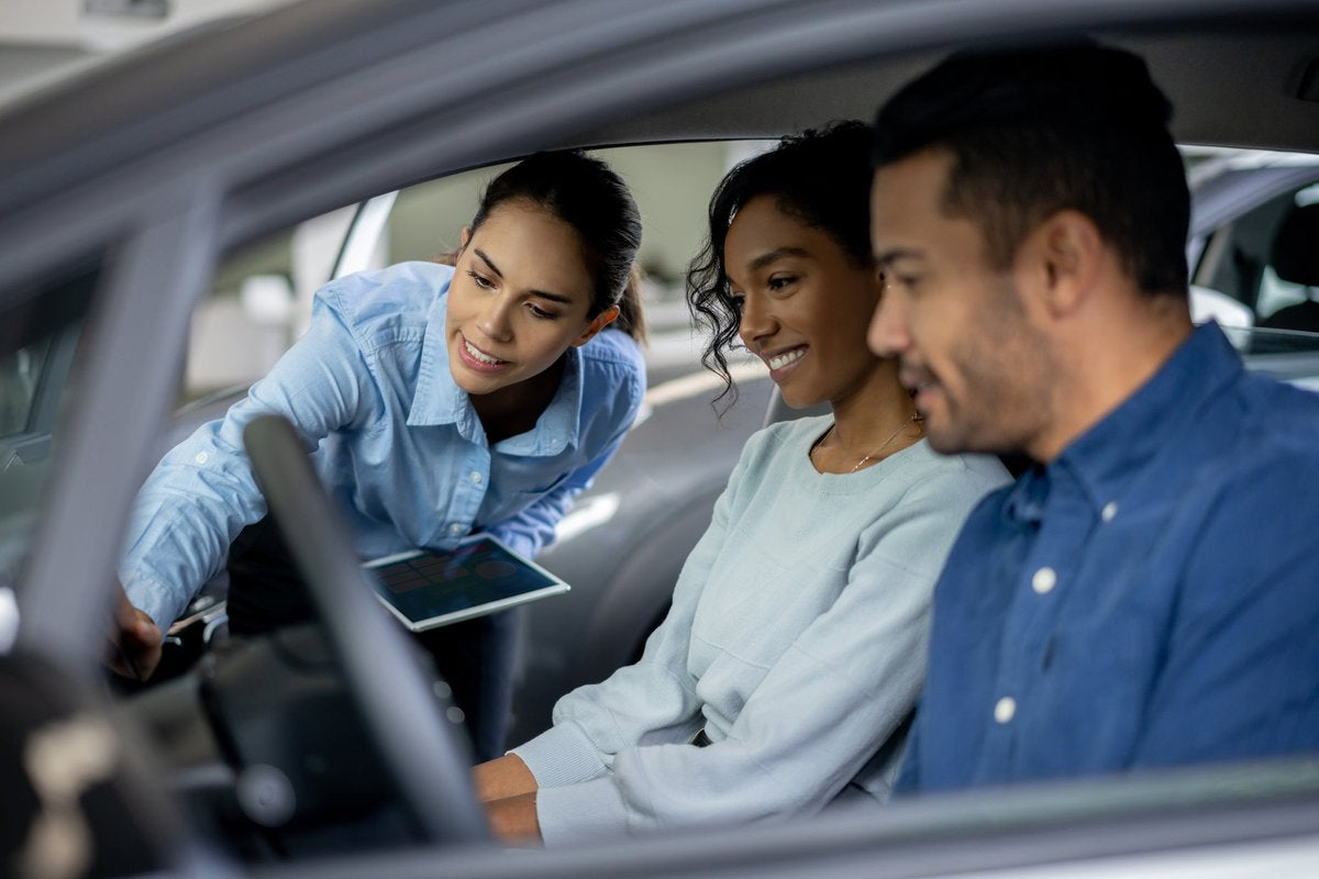 Salesperson showing couple features inside a car.