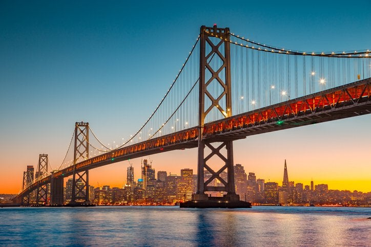 A view of San Francisco at sunset from across the water with the Bay Bridge in the foreground.