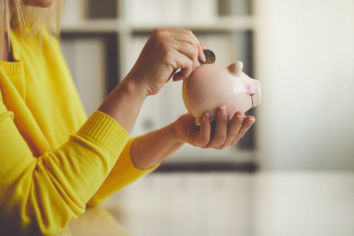 woman's hand inserting quarter into piggy bank