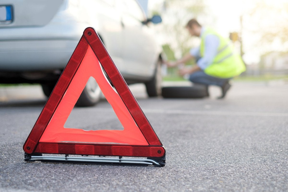 A road caution triangle in front of a man changing a car tire