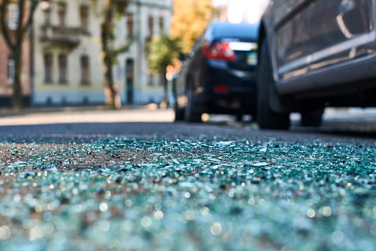Shattered glass on a street next to parked cars.