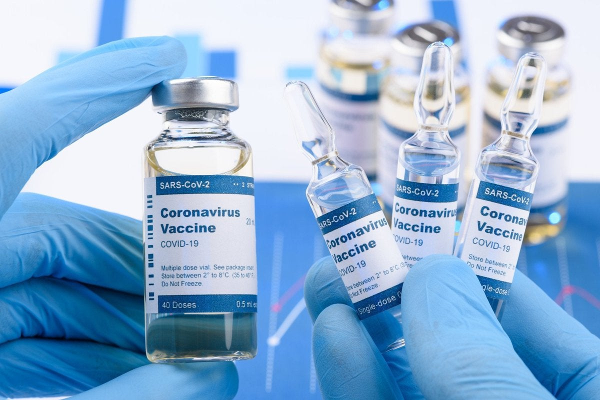 Medical worker with blue gloves holding vials labeled Coronavirus Vaccine.