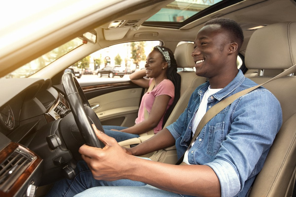 A smiling couple are in a car, enjoying the sunny day.